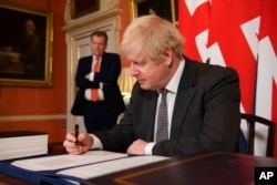UK chief trade negotiator David Frost looks on as Britain's Prime Minister Boris Johnson signs the EU-UK Trade and Cooperation Agreement at 10 Downing Street, London, Dec. 30, 2020.