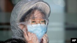 A Chinese woman uses a plastic bag to cover her head while waiting for her flight at the departure area of Manila's International Airport, Philippines on Wednesday, March 18, 2020.