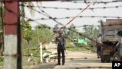 រូបឯកសារ៖ មន្ត្រីប៉ូលិសមីយ៉ាន់ម៉ាម្នាក់កំពុងឈរ នៅពេលដែលអ្នកសារព័ត៌មាន បានទៅដល់ភូមិ Shwe Zar នៅជាយក្រុង Maungdaw ស្ថិតនៅភាគខាងជើងនៃរដ្ឋ Rakhine ប្រទេសមីយ៉ាន់ម៉ា កាលពីឆ្នាំ ២០១៧។