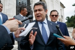 FILE - Honduran President Juan Orlando Hernandez answers questions from the Associated Press, August 13, 2019, as he leaves a meeting of the Organization of American States, in Washington.