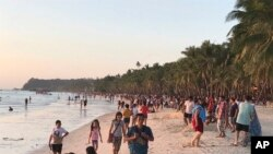 Visitors gather along the beach during sunset in Boracay island, Philippines, Friday, Oct. 26, 2018. Tourists sailed to the popular destination on the first day officials reopened the resort to visitors after a six-month closure to clean waters…