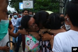 A man is hugged by two women after being released from Insein Prison in Yangon, Myanmar, June 30, 2021. Myanmar's government released about 2,300 prisoners.