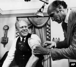 FILE - U.S. President Gerald Ford rolls up his sleeve and receives a swine flu shot from White House physician Dr. William Lukash, Oct. 14, 1976.