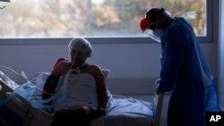 Un trabajador de la salud atiende a un paciente en una unidad de cuidados intensivos designada para personas infectadas con COVID-19 en un hospital en Buenos Aires, Argentina, el viernes 2 de octubre de 2020.