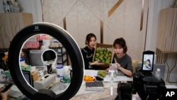 In this May 5, 2020, photo, China's online celebrity Zhang Mofan, right, introduces fresh mangos to her online clients and fans through the live-streaming at her house in Beijing. Retailers in China are embracing livestreaming as a sales channel…