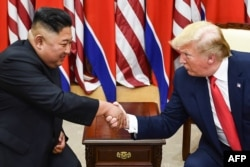 FILE -- In this file photo taken on June 30, 2019, North Korea's leader Kim Jong Un and US President Donald Trump shake hands during a meeting on the south side of the Military Demarcation Line that divides North and South Korea.