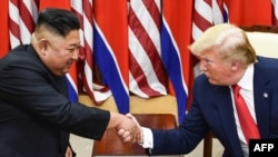 (FILES) In this file photo taken on June 30, 2019, North Korea's leader Kim Jong Un (L) and US President Donald Trump shake hands during a meeting on the south side of the Military Demarcation Line that divides North and South Korea, in the Joint…