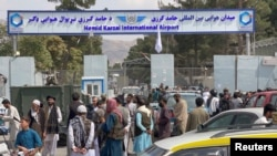 FILE - People gather at the entrance gate of Hamid Karzai International Airport a day after U.S troops withdrawal, in Kabul, Afghanistan, August 31, 2021.
