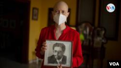 Cristhian Tinoco, hija del exvicecanciller Victor Hugo Tinoco, sostiene una fotografía de su padre, detenido hace una semana en Nicaragua. [Foto: VOA]