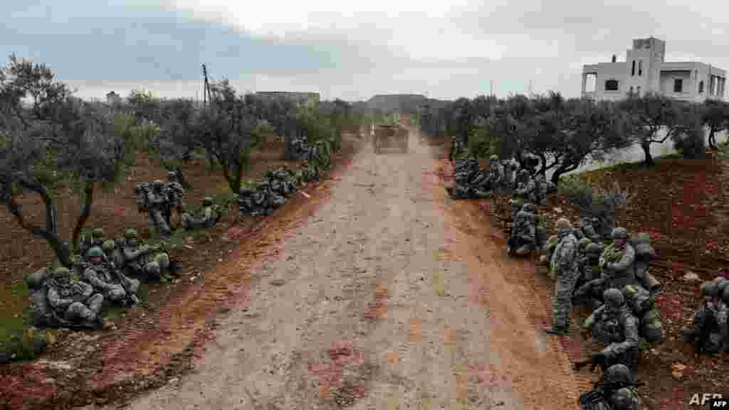 시리아 이들리브에서 남동쪽으로 6km 떨어진 곳에 위치한 콰미나스 마을에 터키 군인들이 앉아 있다