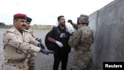 Un soldado estadounidense verifica la temperatura de un fotógrafo de prensa, luego del brote de la enfermedad por coronavirus (COVID-19), antes de una ceremonia de entrega de la base aérea K-1 de las fuerzas de la coalición liderada por los EE.UU.