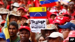 """A demonstrator holds a sign with a message that reads in Spanish: """"Trump unblock Venezuela"""" as members of the Bolivarian militia attend a protest against U.S. sanctions on Venezuela, in Caracas, Venezuela, Aug. 7, 2019."""