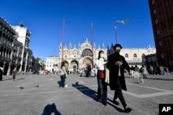 Tourists walk in St. Mark's Square in Venice, Italy, Feb. 28, 2020.
