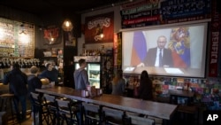 A few visitors and staff of the pub watching the broadcast of Russian President Vladimir Putin addresses Russian citizens on the State Television channels in Moscow, Russia, March 25, 2020.