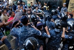 Anti-government protesters clash with riot police in front of the Ministry of Economy in downtown Beirut, Lebanon, Monday, May 11, 2020.