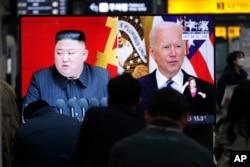 Gambar pemimpin Korea Utara Kim Jong Un dan Presiden AS Joe Biden selama siaran berita di Stasiun Kereta Api Suseo di Seoul, Korea Selatan, 26 Maret 2021. (Foto: AP)