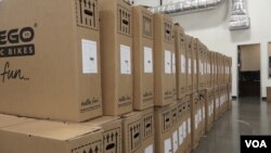 Boxes of bikes from Vietnam are stacked in the warehouse of Pedego Electric Bikes in Fountain Valley, California. The bikes are assembled at the company's headquarters. (VOA/E. Lee)