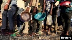 Des réfugiés éthiopiens ayant fui la région du Tigré font la queue pour recevoir une aide alimentaire dans le camp d'Um-Rakoba dans l'État d'Al-Qadarif, à la frontière, au Soudan, le 11 décembre 2020.