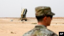 FILE - A member of the U.S. Air Force stands near a Patriot missile battery at the Prince Sultan air base in al-Kharj, central Saudi Arabia, Feb. 20, 2020.