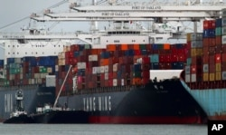 FILE -The Yang Ming shipping line container ship Ym Utmost is unloaded at the Port of Oakland on Monday, July 2, 2018, in Oakland, Calif.
