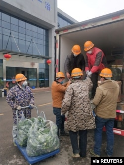 FILE - Construction workers building a temporary hospital receive meat and vegetables delivered by Wuhan resident Chen Hui and another volunteer in Ezhou, Hubei province, China, Feb. 11, 2020.