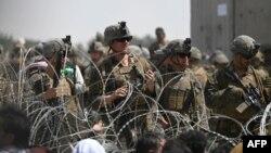 Tentara AS berjaga di balik kawat berduri saat warga Afghanistan duduk di pinggir jalan dekat bagian militer bandara di Kabul, 20 Agustus 2021.(Foto: AFP)
