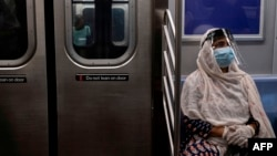 (FILES) In this file photo taken on July 16, 2020, a woman wearing a face mask and shield sits in a subway train during rush hour amid the coronavirus pandemic in New York City. - The US Centers for Disease Control and Prevention have issued a…