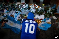 A fan mourns in front of flowers and posters left in tribute to Diego Maradona at the entrance of the Boca Juniors stadium known as La Bombonera in Buenos Aires, Argentina, Nov. 27, 2020. Maradona died Nov. 25 at age 60.
