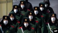 ប៉ូលិសប៉ារ៉ាពាក់ម៉ាស់ នៅពេលដើរក្បួនមួយនៅជាប់ទីលាន Tiananmen ក្នុងក្រុងប៉េកាំង កាលពីថ្ងៃទី៤ ខែកុម្ភៈ ឆ្នាំ២០២០។