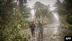 Residents brave rains and strong wind as they walk past uprooted trees along a highway in Can-avid town, Eastern Samar province, central Philippines, May 14, 2020, as Typhoon Vongfong makes landfall.