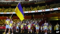 Olena Kostevych and Bogdan Nikishin, of Ukraine, carry their country's flag during the opening ceremony in the Olympic Stadium at the 2020 Summer Olympics, July 23, 2021, in Tokyo, Japan.