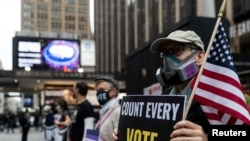 FILE - A man wearing a protective mask due to COVID-19 pandemic holds a sign outside Madison Square Garden, which is used as a polling station, on the first day of early voting in Manhattan, New York, Oct. 24, 2020.