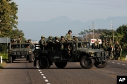 Mexican National Guards block a highway in Ciudad Hidalgo, Mexico after a group of Central American migrants crossed the nearby border from Guatemala to Mexico, Jan. 23, 2020.