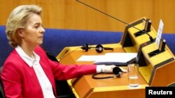 European Commission President Ursula von der Leyen wears protective gloves during a special session of the European Parliament to approve special measures to soften the sudden economic impact of COVID-19, in Brussels, Belgium, March 26, 2020.
