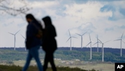 People are silhouetted as they stroll past power generating wind turbines visible from a walking path at the Flight 93 National Memorial in Shanksville, Pa., Saturday, May 8, 2021. (AP Photo/Keith Srakocic)