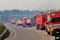 A convoy of firetrucks use a road during a wildfire in Lalas village, near Olympia town, western Greece, Aug. 5, 2021.