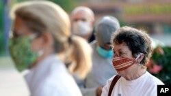 지난달 27일 미국 텍사스주 휴스턴의 슈퍼마켓 앞에 마스크를 착용한 시민들이 줄 서 있다.