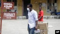 A man wearing face mask walks at the Yaba Mainland hospital where an Italian citizen who entered Nigeria on Tuesday from Milan on a business trip, the first case of the COVID-19 virus is being treated in Lagos Nigeria, Feb. 28, 2020.