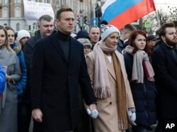 In this photo taken on Saturday, March 29, 2020, Russian opposition activist Alexei Navalny, center left, and his wife Yulia, take part in a march in memory of opposition leader Boris Nemtsov in Moscow, Russia. Russian opposition leader Alexei…