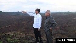 ປະທານາທິບໍດີ Joko Widodo ຂອງອິນໂດເນເຊຍຊີ້ມືໃຫ້ເຈົ້າແຂວງເກາະ Kalimantan Isran Noor ຕາເວັນອອກທີ່ຢືນຂ້າງທ່ານນັ້ນເບິ່ງ ໃນຂະນະທີ່ໄປຢ້ຽມບ່ອນທີ່ຈະຕັ້ງນະຄອນຫລວງໃໝ່ຂອງອິນໂດເນເຊຍຢູ່ເມືອງ Sepaku ເໜືອ, ເຂດ Penajam Paser, ເກາະ Kalimantan ຕາເວັນອອກນັ້ນ