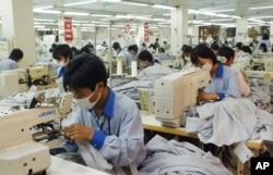 FILE - In this photo from 2007, workers sew shirts to be exported to the United States at Garment Co. 10 outside Hanoi, Vietnam. Today,Malaysia, Indonesia, Vietnam and other countries in the region are being forced to respond to the surging coronavirus caseloads with factory shutdowns and stricter lockdown and social distancing rules.