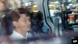 Pro-democracy activists Joshua Wong, left, and Agnes Chow, are escorted in a police van at a district court in Hong Kong, Aug. 30, 2019.