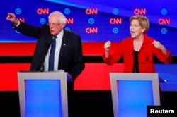 U.S. Senators Bernie Sanders, left, and Elizabeth Warren speak on the first night of the second 2020 Democratic presidential debate in Detroit, Michigan, July 30, 2019.