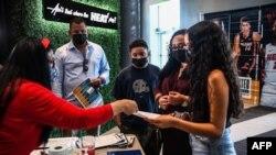 Lorena Torres (2R) madre de Valentina Jiménez (derecha) de 15 años es asistida por el personal de Miami Heat durante un evento de vacunación COVID-19 organizado por Miami Heat en FTX Arena en Miami, el 5 de agosto de 2021.
