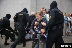 Law enforcement officers scuffle with demonstrators during a rally in support of detained Belarusian opposition leader Maria Kolesnikova in Minsk, Belarus, Sept. 8, 2020.