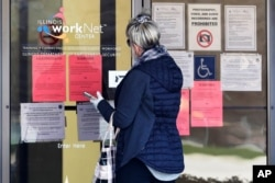 FILE - A woman checks job application information in front of IDES(Illinois Department of Employment Security)/WorkNet center in Arlington Heights, Ill., April 9, 2020.
