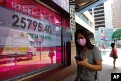A woman walks past a bank electronic board showing the Hong Kong share index outside a Hong Kong local bank, Aug. 31, 2020.