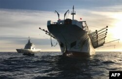 """FILE - A handout picture released by Argentina's Navy press office shows the ARA """"Bouchard"""" Ocean Patrol escorting a Chinese-flagged fishing ship after it was caught illegally operating in Argentina's Exclusive Economic Zone, May 4, 2020."""