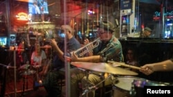 The Catahoula Music Company performs behind protective plexiglass at Maison Bourbon as the coronavirus disease (COVID-19) restrictions are eased in New Orleans, Louisiana, March 13, 2021.