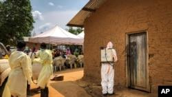Un employé de l'Organisation mondiale de la santé décontamine l'entrée d'une maison située dans une parcelle où deux cas d'Ebola ont été découverts, dans le village de Mabalako, dans l'est du Congo, le 17 juin 2019.